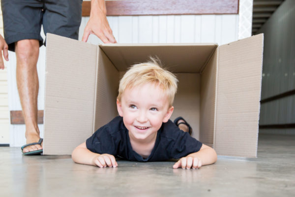 Child poking out of box while laying down at Cairns Beaches Storage sheds.
