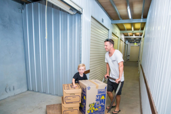 customer with child pushing moving boxes into storage unit at cairns Beaches Storage