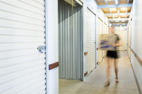 Staff member placing box into storage shed at Cairns Beaches Storage
